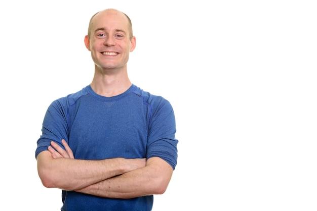 Homem branco careca feliz sorrindo com os braços cruzados