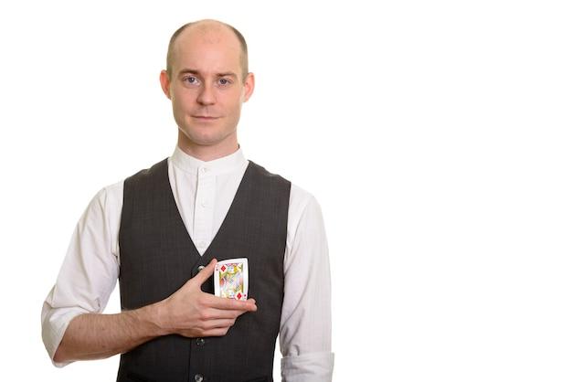 Homem branco careca, mágico, dobrando cartão do valete de ouros