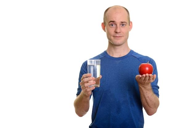 Homem branco careca segurando um copo d'água e uma maçã vermelha