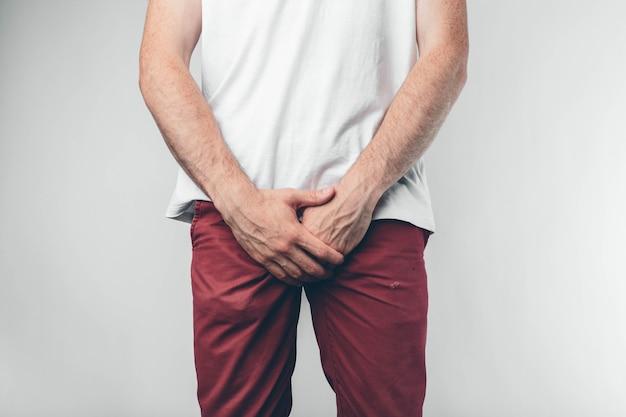 Homem branco com camiseta branca e calça cor de vinho. mantém as mãos na virilha. vista de corte. conceito.