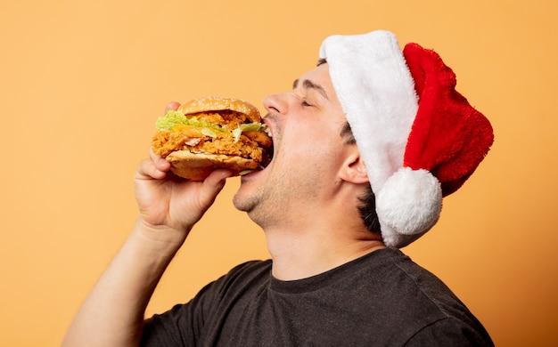 Homem branco com camiseta preta e chapéu de papai noel com hambúrguer na parede amarela