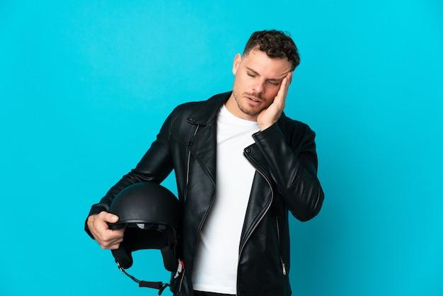 Homem branco com capacete de motociclista isolado em azul com dor de cabeça
