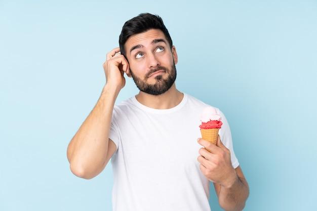 Homem branco com um sorvete de corneta isolado na parede azul, tendo dúvidas e com expressão facial confusa