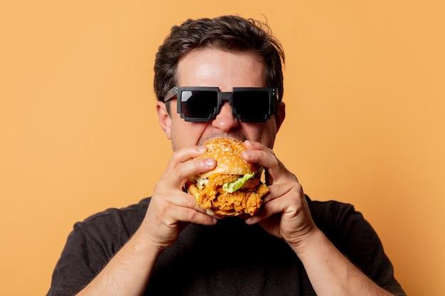 Homem branco de camiseta preta com hambúrguer na parede amarela