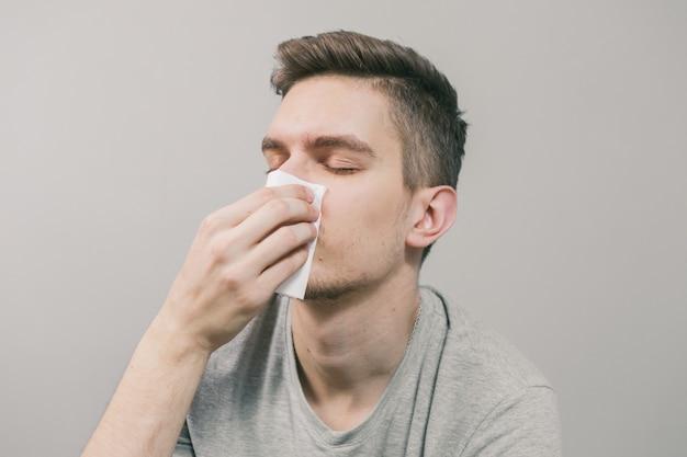 Homem branco fica doente e assoa o nariz em um guardanapo branco