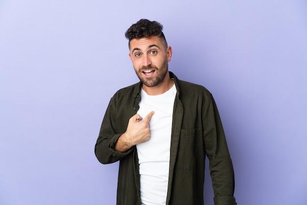 Homem branco isolado em um fundo roxo com expressão facial surpresa