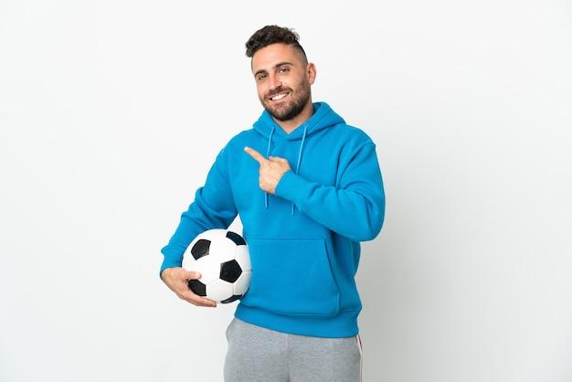 Homem branco isolado no fundo branco com bola de futebol e apontando para a lateral