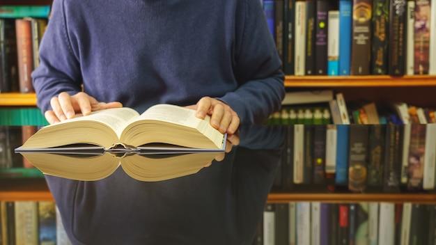 Homem branco lendo livro em uma mesa de vidro e uma livraria com muitos livros.