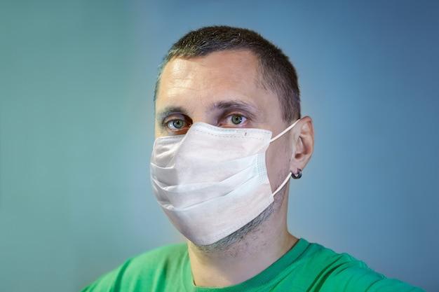 Homem branco sério, branco, usando máscara cirúrgica facial protetora como proteção durante a infecção pandêmica por coronavírus covid-19.