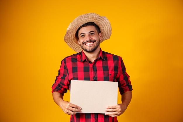 Homem brasileiro com roupas típicas da festa junina segurando cartaz