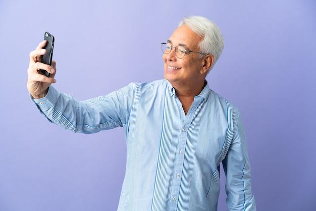 Homem brasileiro de meia-idade isolado em fundo roxo fazendo selfie