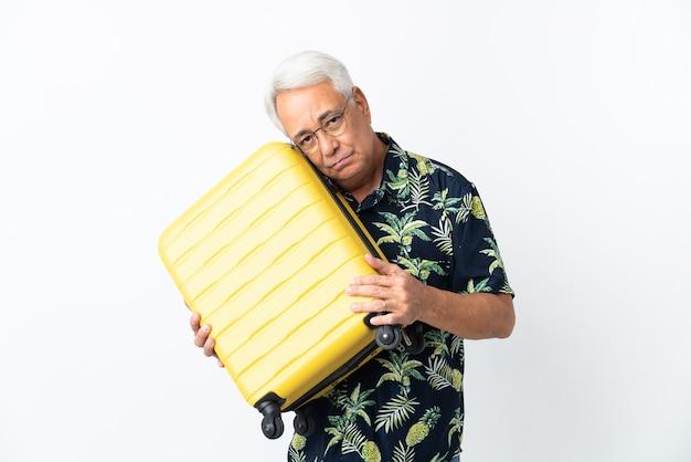 Homem brasileiro de meia-idade isolado no fundo branco em férias com mala de viagem e infeliz