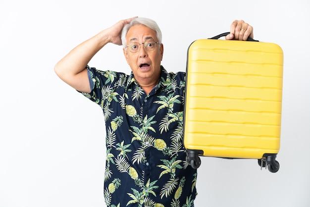 Homem brasileiro de meia-idade isolado no fundo branco em férias com mala de viagem e surpreso