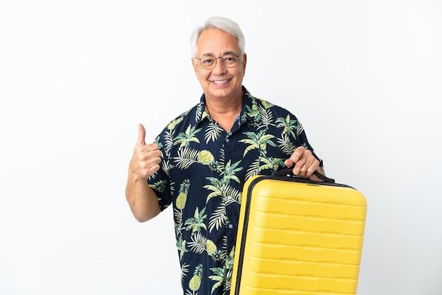 Homem brasileiro de meia-idade isolado no fundo branco nas férias com mala de viagem e polegar para cima