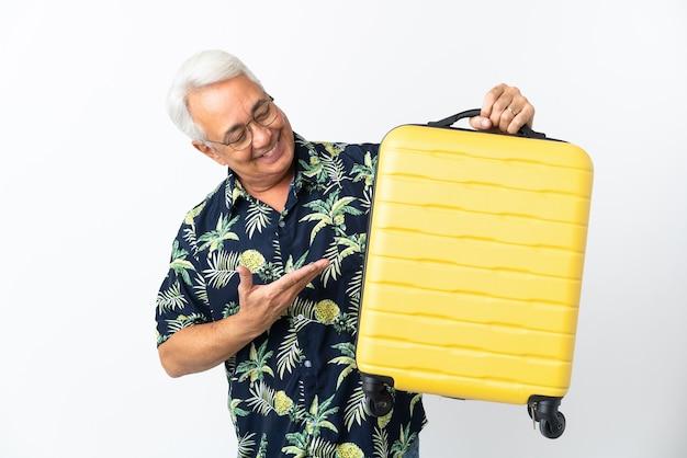Homem brasileiro de meia-idade isolado no fundo branco nas férias com mala de viagem