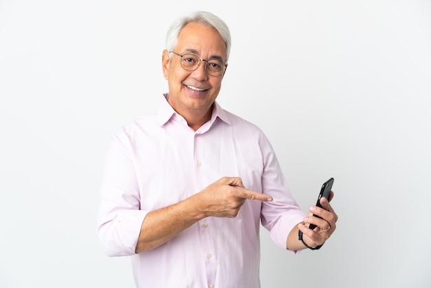 Homem brasileiro de meia-idade isolado no fundo branco usando celular e apontando