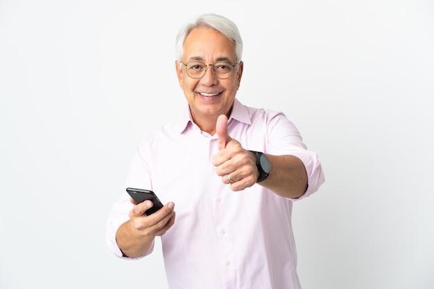 Homem brasileiro de meia-idade isolado no fundo branco, usando telefone celular enquanto faz o polegar para cima