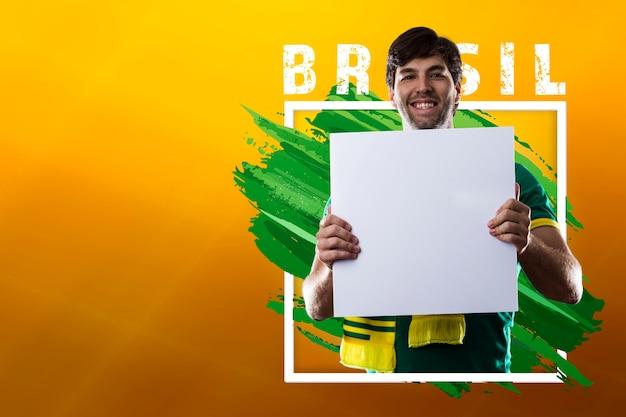 Homem brasileiro feliz, fã de futebol segurando cartaz em branco