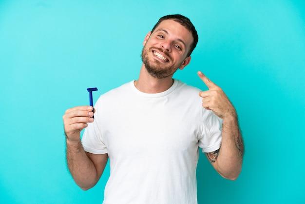 Homem brasileiro raspando a barba isolada em um fundo azul fazendo um gesto de polegar para cima