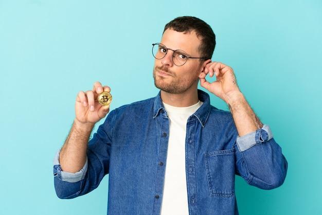 Homem brasileiro segurando um bitcoin sobre fundo azul isolado com dúvidas
