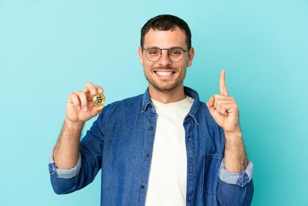 Homem brasileiro segurando um bitcoin sobre fundo azul isolado, mostrando e levantando um dedo em sinal dos melhores