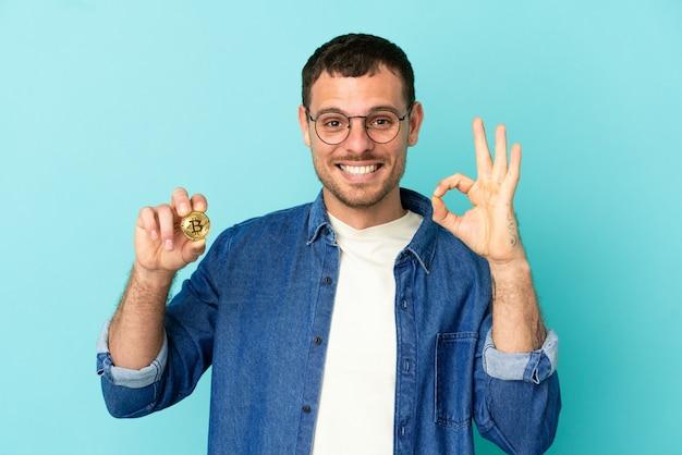 Homem brasileiro segurando um bitcoin sobre fundo azul isolado, mostrando sinal de ok com os dedos