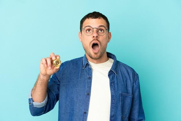 Homem brasileiro segurando um bitcoin sobre fundo azul isolado olhando para cima e com expressão de surpresa