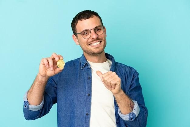 Homem brasileiro segurando um bitcoin sobre fundo azul isolado orgulhoso e satisfeito consigo mesmo