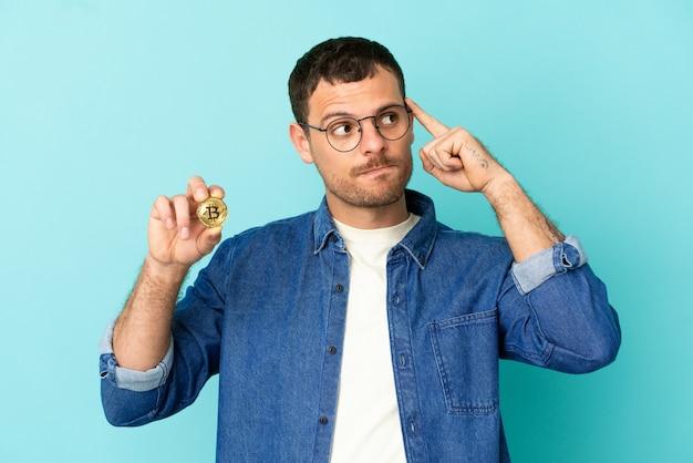 Homem brasileiro segurando um bitcoin sobre fundo azul isolado, tendo dúvidas e pensando
