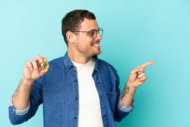 Homem brasileiro segurando um bitcoin sobre um fundo azul isolado apontando o dedo para o lado e apresentando um produto