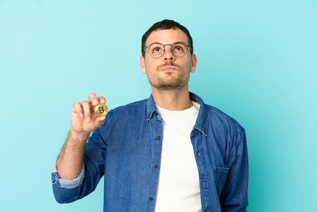 Homem brasileiro segurando um bitcoin sobre um fundo azul isolado e olhando para cima