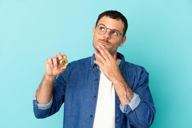 Homem brasileiro segurando um bitcoin sobre um fundo azul isolado, olhando para cima enquanto sorri