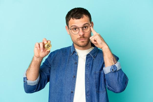 Homem brasileiro segurando um bitcoin sobre um fundo azul isolado pensando uma ideia