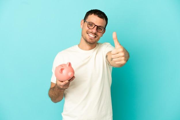 Homem brasileiro segurando um cofrinho sobre um fundo azul isolado com o polegar para cima porque algo bom aconteceu