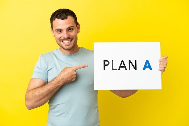 Homem brasileiro sobre fundo roxo isolado segurando um cartaz com a mensagem plano a e apontando-o
