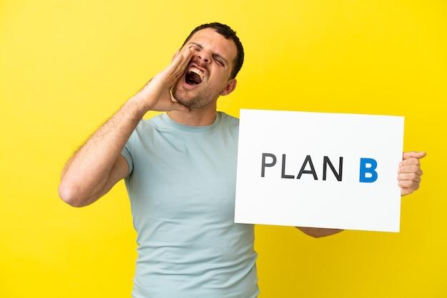 Homem brasileiro sobre fundo roxo isolado segurando um cartaz com a mensagem plano b e gritando
