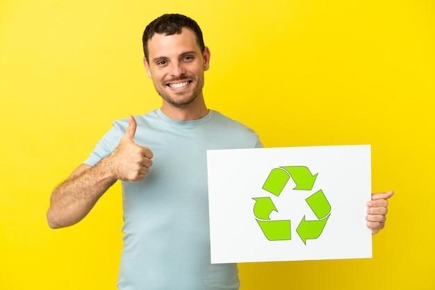 Homem brasileiro sobre fundo roxo isolado segurando um cartaz com o ícone de reciclagem com o polegar para cima