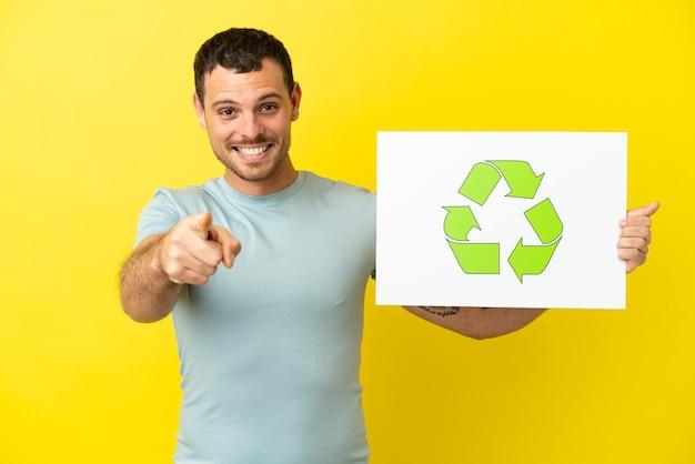 Homem brasileiro sobre fundo roxo isolado segurando um cartaz com o ícone de reciclagem e apontando para a frente