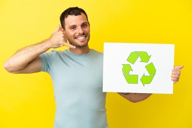 Homem brasileiro sobre fundo roxo isolado segurando um cartaz com o ícone de reciclagem e fazendo gestos de telefone