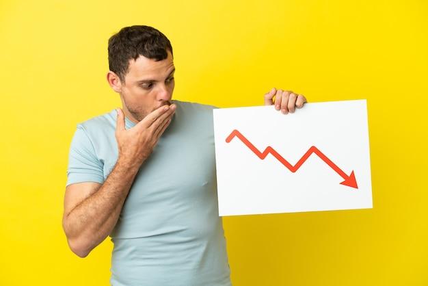 Homem brasileiro sobre fundo roxo isolado segurando uma placa com uma seta de estatística decrescente com expressão de surpresa