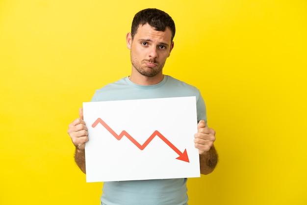 Homem brasileiro sobre fundo roxo isolado segurando uma placa com uma seta de estatística decrescente com expressão triste