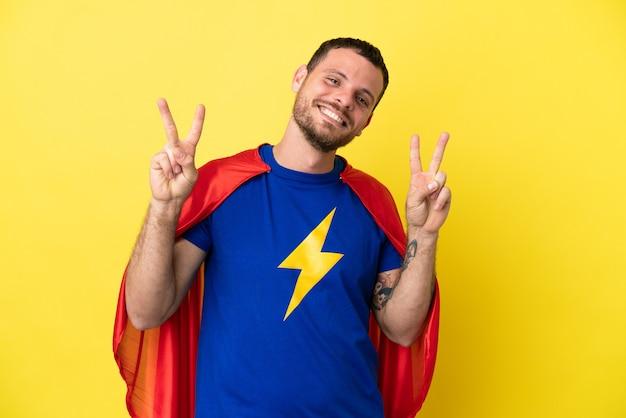 Homem brasileiro super-herói isolado em fundo amarelo mostrando sinal de vitória com as duas mãos