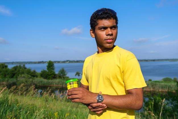 Homem brasileiro tomando café ao ar livre no verão perto do rio