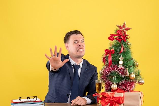 Homem bravo de frente, fazendo sinal de pare, sentado à mesa perto da árvore de natal e presentes em fundo amarelo