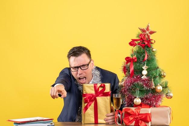 Homem bravo de vista frontal apontando para a câmera sentado à mesa perto da árvore de natal e presentes em fundo amarelo