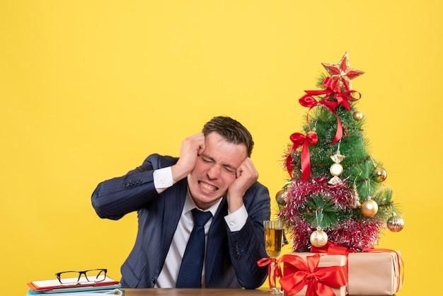 Homem bravo de vista frontal, segurando sua cabeça sentado à mesa perto da árvore de natal e presentes em fundo amarelo