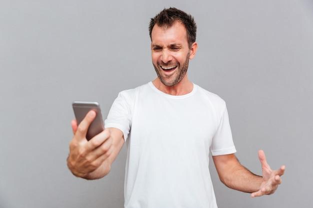 Homem bravo e casual segurando um smartphone isolado em um fundo cinza