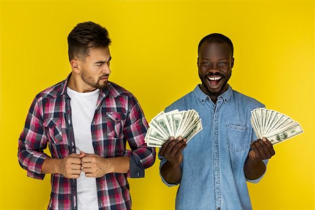 Homem bravo e feliz homem detém dólares
