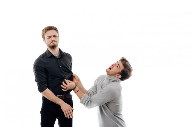 Homem bravo se afasta de um cara enquanto ele estende as mãos para tentar segurá-la, espaço em branco isolado, cópia espaço