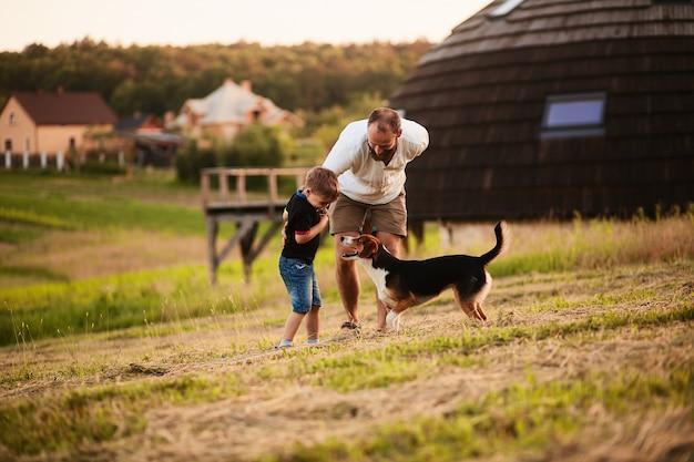 Homem brinca com seu filho e um cachorro no campo